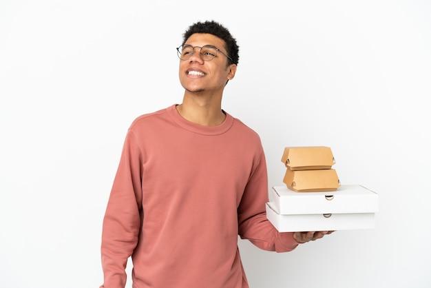 Молодой афроамериканец, держащий гамбургер и пиццу, изолированные на белом фоне, думает об идее, глядя вверх
