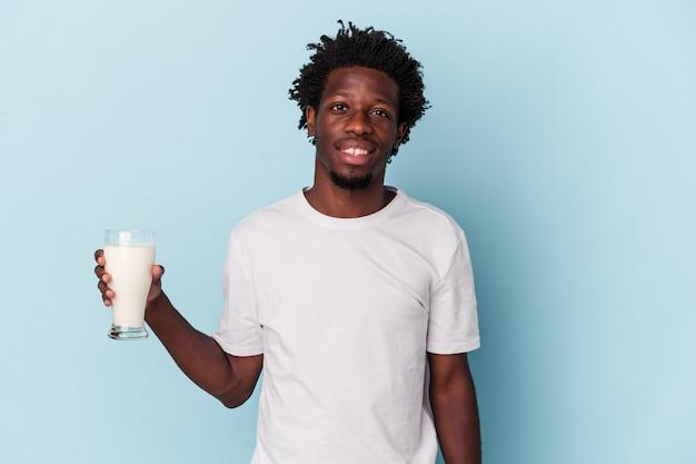 幸せ、笑顔、陽気な青い背景で隔離のミルクのガラスを保持している若いアフリカ系アメリカ人の男。