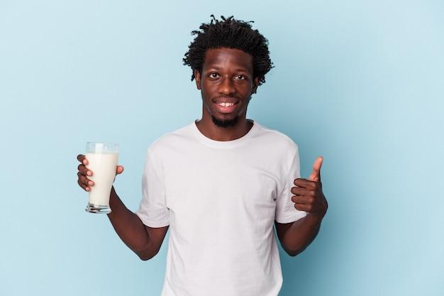 笑顔と親指を上げて青い背景で隔離のミルクのガラスを保持している若いアフリカ系アメリカ人の男
