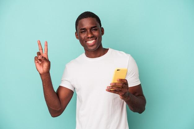 青い背景に隔離された携帯電話を持っている若いアフリカ系アメリカ人の男は、指で平和のシンボルを示して楽しくてのんきです。