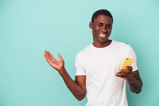 手のひらにコピースペースを示し、腰に別の手を保持している青い背景で隔離の携帯電話を保持している若いアフリカ系アメリカ人の男性。