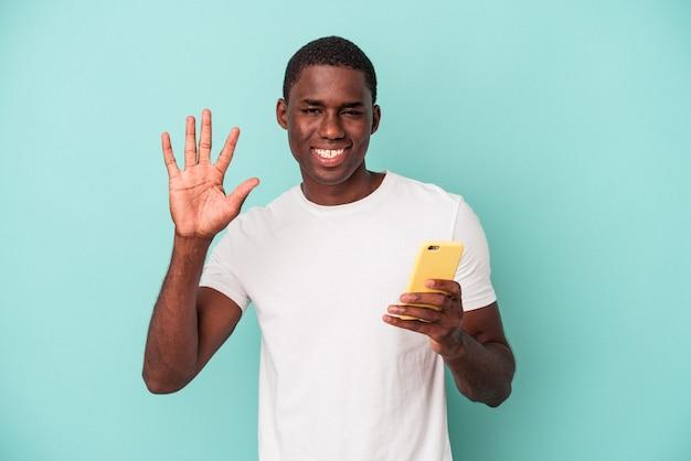 青い背景に分離された携帯電話を持っている若いアフリカ系アメリカ人の男は、指で5番を示して陽気に笑っています。