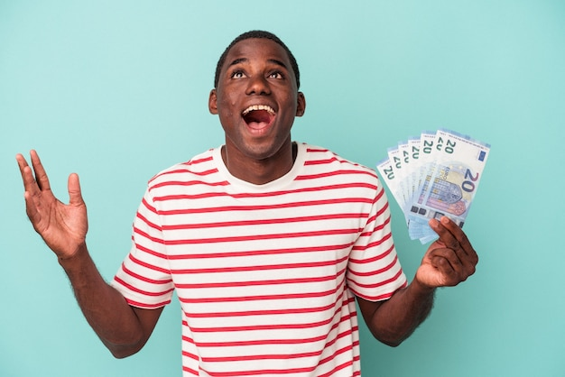 Young african american man holding a bank notes isolated on blue background receiving a pleasant surprise, excited and raising hands.