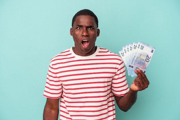 Young african american man holding a bank notes isolated on blue background screaming very angry and aggressive.