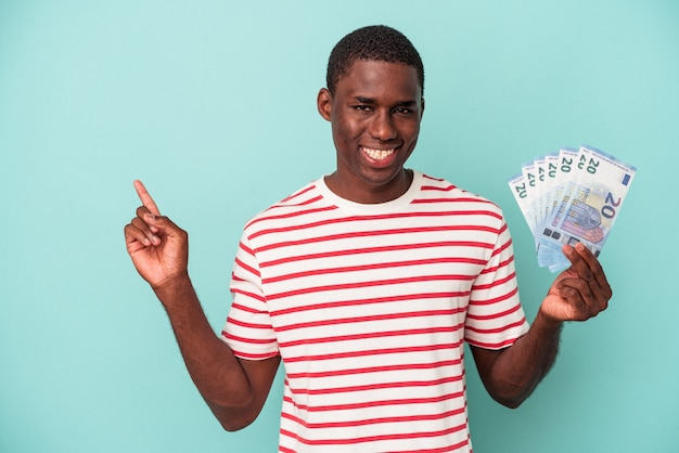 Young african american man holding a bank notes isolated on blue background smiling and pointing aside, showing something at blank space.