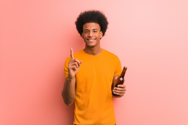 Young african american man holding a beer showing number one