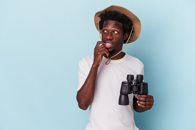 Young african american man holding binoculars isolated on blue background relaxed thinking about something looking at a copy space.