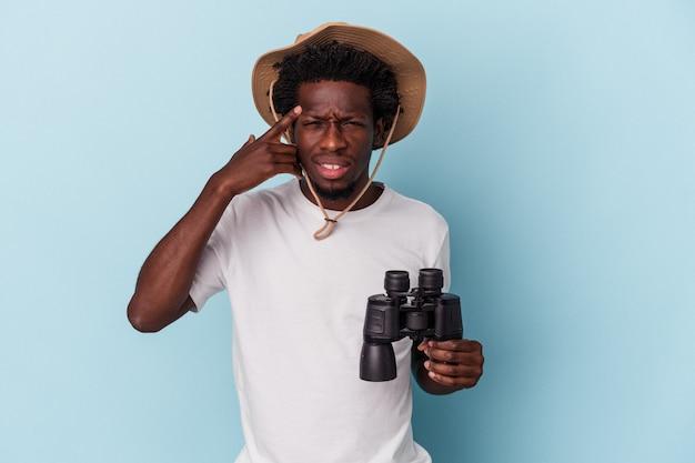 人差し指で失望のジェスチャーを示す青い背景に分離された双眼鏡を保持している若いアフリカ系アメリカ人の男。
