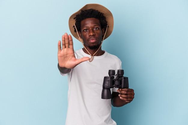 青の背景に分離された双眼鏡を持っている若いアフリカ系アメリカ人の男は、一時停止の標識を示している手を伸ばして立って、あなたを妨げています。