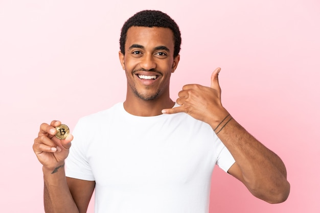 Young african american man holding a bitcoin over isolated pink background making phone gesture. call me back sign