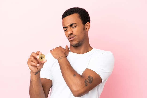 Young african american man holding a bitcoin over isolated pink surface suffering from pain in shoulder for having made an effort