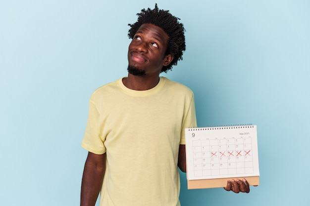 Young african american man holding calendar isolated on blue background dreaming of achieving goals and purposes