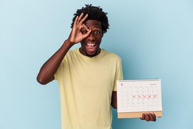 Молодой афро-американский мужчина, держащий календарь, изолированный на синем фоне, взволнован, держа хорошо жест на глазах.