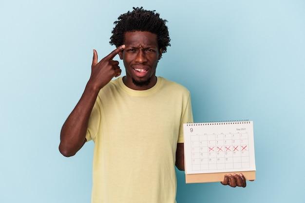 人差し指で失望のジェスチャーを示す青い背景で隔離のカレンダーを保持している若いアフリカ系アメリカ人の男。