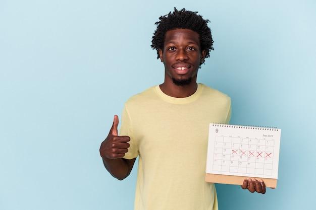 Молодой афро-американский мужчина держит календарь, изолированный на синем фоне, улыбается и поднимает палец вверх