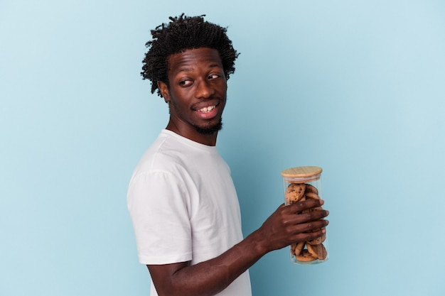 Young african american man holding chocolate chips cookies isolated on blue background looks aside smiling, cheerful and pleasant.
