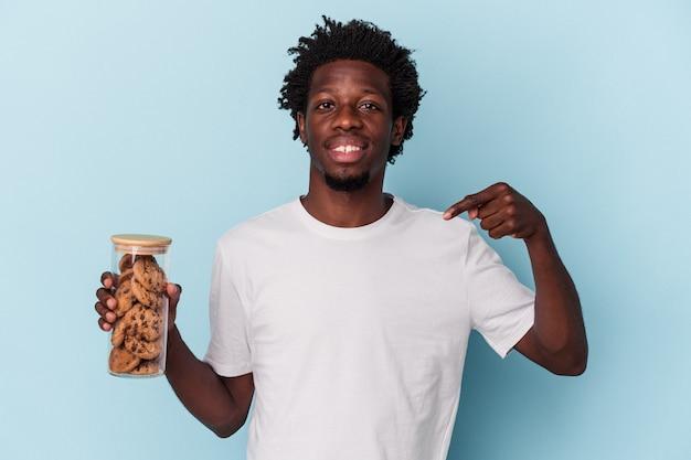 誇りと自信を持って、シャツのコピースペースを手で指している青い背景の人に分離されたチョコレートチップクッキーを保持している若いアフリカ系アメリカ人の男
