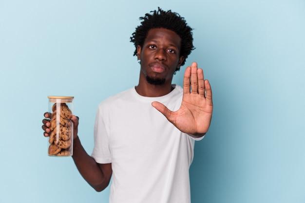 青の背景に分離されたチョコレートチップクッキーを保持している若いアフリカ系アメリカ人の男は、一時停止の標識を示している手を伸ばして立って、あなたを防ぎます。