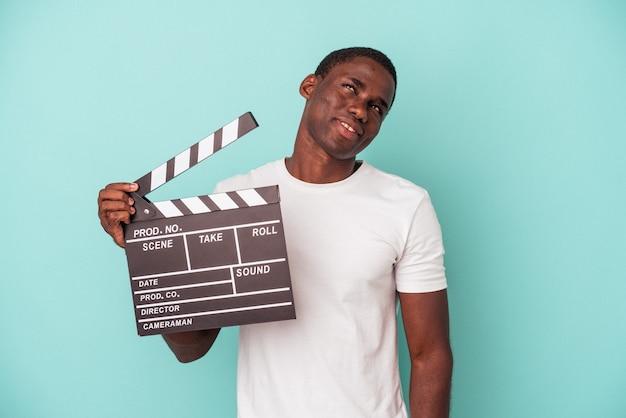 目標と目的を達成することを夢見て青い背景で隔離のカチンコを保持している若いアフリカ系アメリカ人の男