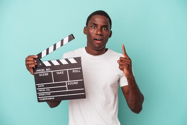 파란색 배경에 격리된 클래퍼보드를 들고 있는 젊은 아프리카계 미국인 남자는 훌륭한 아이디어, 창의성 개념을 가지고 있습니다.