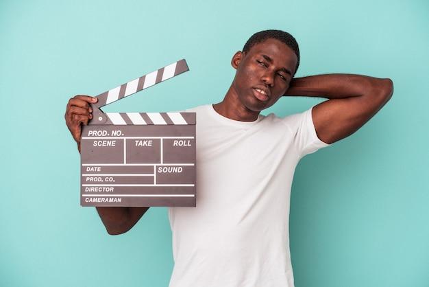 파란색 배경에 격리된 클래퍼보드를 들고 머리 뒤쪽을 만지고 생각하고 선택하는 젊은 아프리카계 미국인 남자.