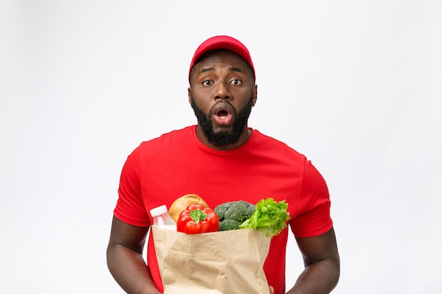 Young african american man holding grocery package in hands with shocking face.