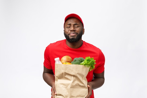 Young african american man holding grocery package in hands