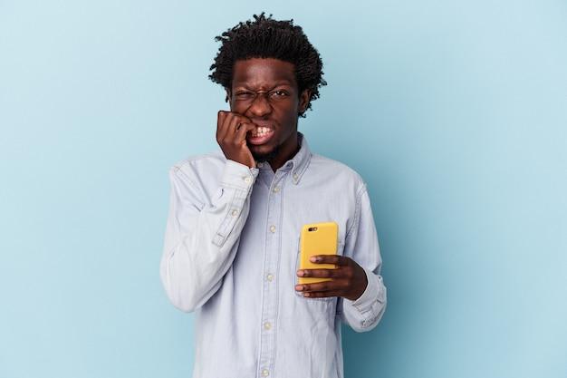 青い背景に隔離された携帯電話を持っている若いアフリカ系アメリカ人の男は、神経質で非常に不安な指の爪を噛んでいます。