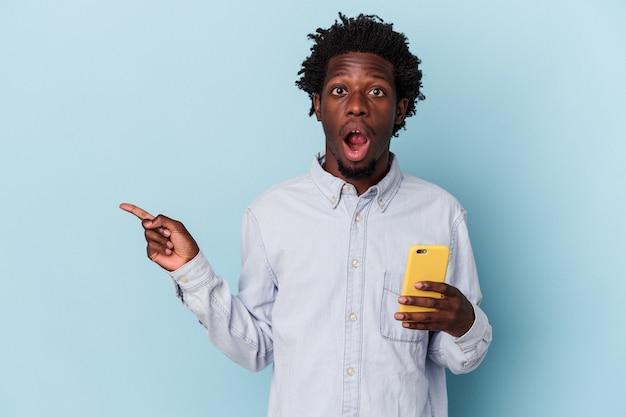 측면을 가리키는 파란색 배경에 고립 된 휴대 전화를 들고 젊은 아프리카 계 미국인 남자