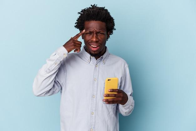 人差し指で失望のジェスチャーを示す青い背景で隔離の携帯電話を保持している若いアフリカ系アメリカ人の男。