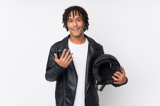 Young african american man holding a motorcycle helmet isolated on white wall inviting to come with hand. happy that you came