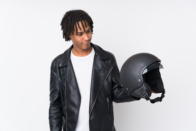 Young african american man holding a motorcycle helmet on white wall with sad expression
