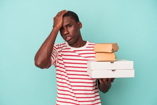 ショックを受けている青い背景に分離されたピザやハンバーガーを保持している若いアフリカ系アメリカ人の男、彼女は重要な会議を覚えています。