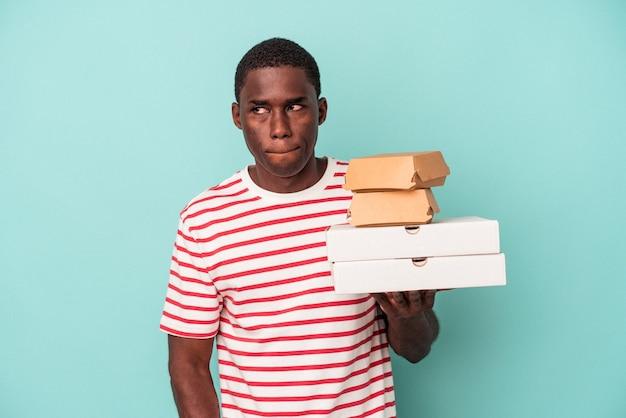 青い背景で隔離のピザやハンバーガーを保持している若いアフリカ系アメリカ人の男は混乱し、疑わしく、不安を感じています。