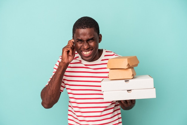 手で耳を覆う青い背景で隔離のピザやハンバーガーを保持している若いアフリカ系アメリカ人の男。