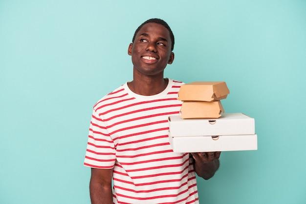 目標と目的を達成することを夢見て青い背景で隔離のピザやハンバーガーを保持している若いアフリカ系アメリカ人の男