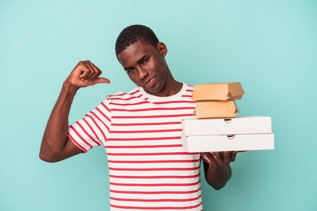 青い背景に分離されたピザやハンバーガーを持っている若いアフリカ系アメリカ人の男性は、誇りと自信を持って、次の例を示します。