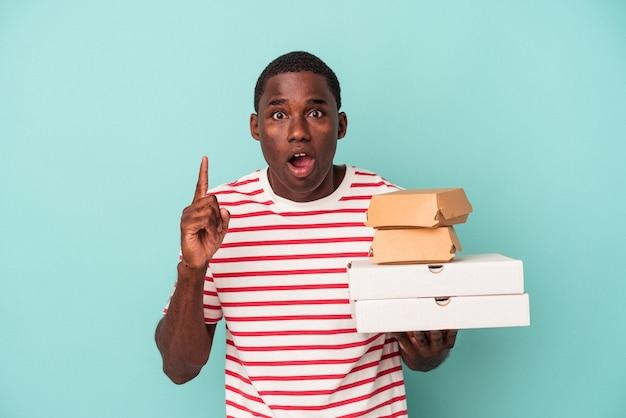 アイデア、インスピレーションのコンセプトを持つ青い背景で隔離のピザやハンバーガーを保持している若いアフリカ系アメリカ人の男。