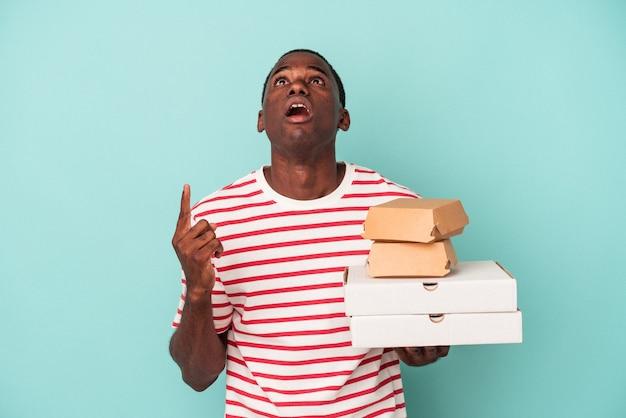 開いた口で逆さまを指している青い背景に分離されたピザやハンバーガーを保持している若いアフリカ系アメリカ人の男。