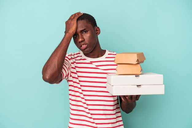Young african american man holding pizzas and burgers isolated on blue background being shocked, she has remembered important meeting.