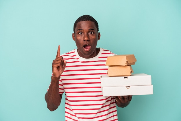 Young african american man holding pizzas and burgers isolated on blue background having an idea, inspiration concept.