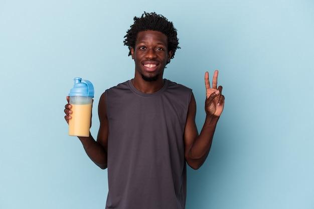 指で2番目を示す青い背景に分離されたタンパク質ミルクセーキを保持している若いアフリカ系アメリカ人男性。