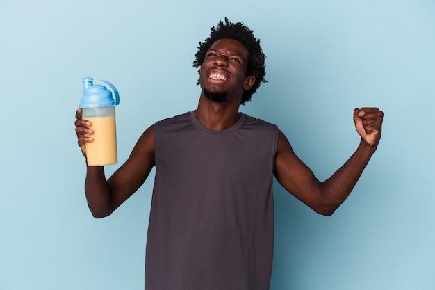 青い背景で隔離のタンパク質ミルクセーキを保持している若いアフリカ系アメリカ人の男