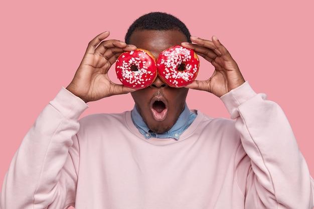 おいしいドーナツを保持している若いアフリカ系アメリカ人の男