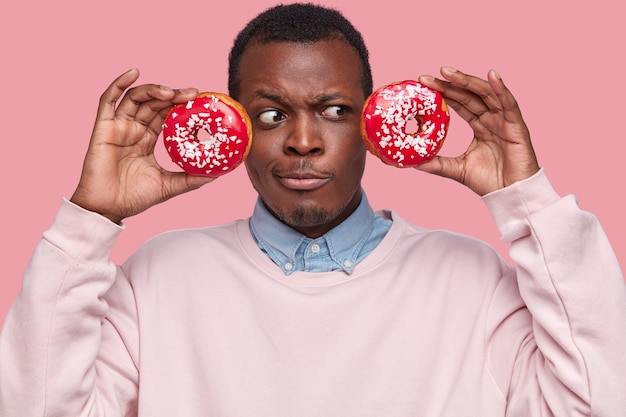 Giovane uomo afroamericano che tiene gustose ciambelle