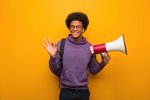 Young african american man holdinga a megaphone cheerful and confident doing ok gesture