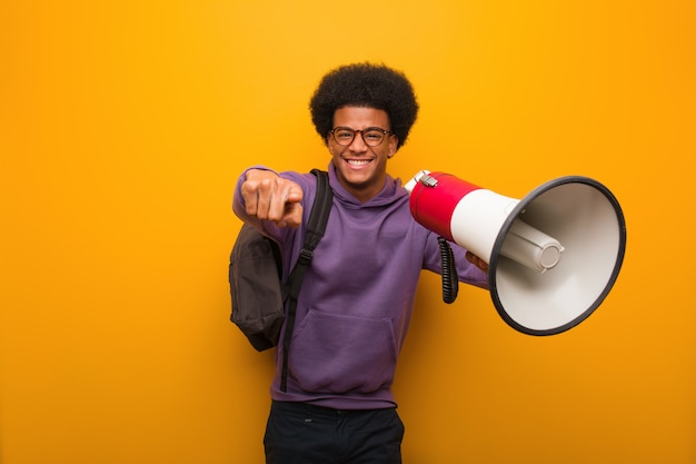 Young african american man holdinga a megaphone cheerful and smiling pointing to front