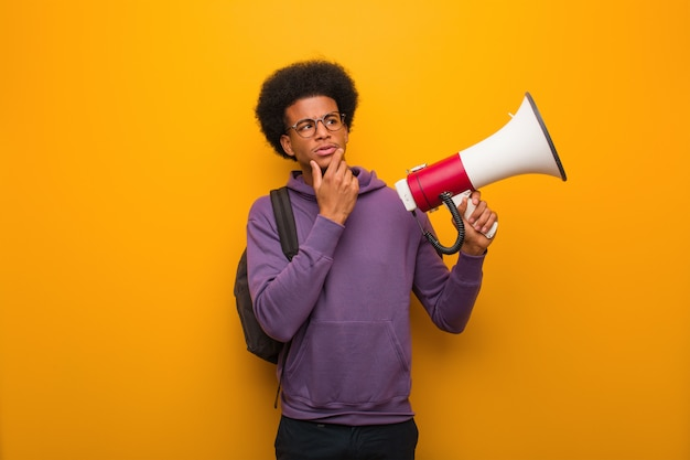 Young african american man holdinga a megaphone doubting and confused