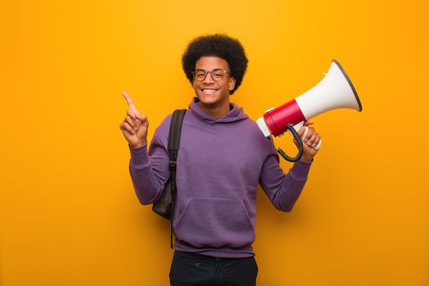 Young african american man holdinga a megaphone pointing to the side with finger