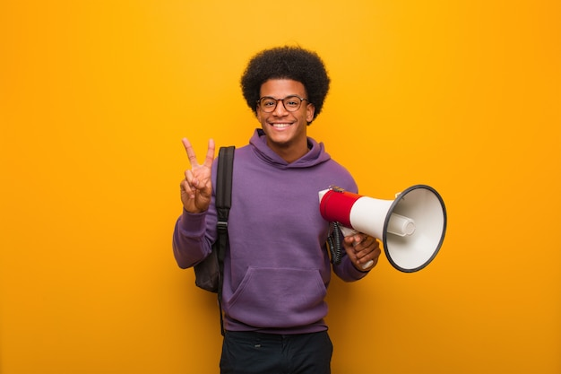 Young african american man holdinga a megaphone showing number two
